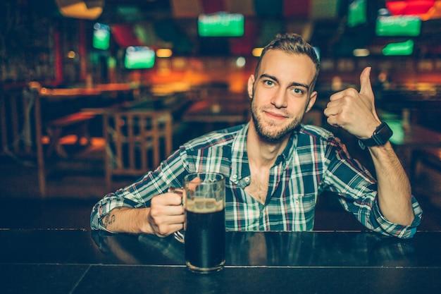 De positieve jonge mens zit bij barteller in bar en ziet eruit. hij houdt een grote duim op. de kerel heeft hand op mok met donker bier.