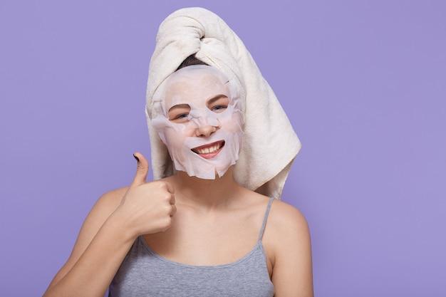 De positieve jonge vrouw toont haar grote duim terwijl het stellen met kosmetisch masker op haar gezicht