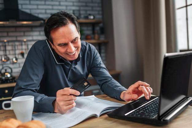 De positieve mens zit bij lijst in keuken. hij praat over de telefoon en kijkt naar kranten. man type op toetsenbord en glimlach.