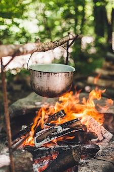 De pot brandt 's nachts bij de tent in het bos. mooi kampvuur in een toeristenkamp in het wild.