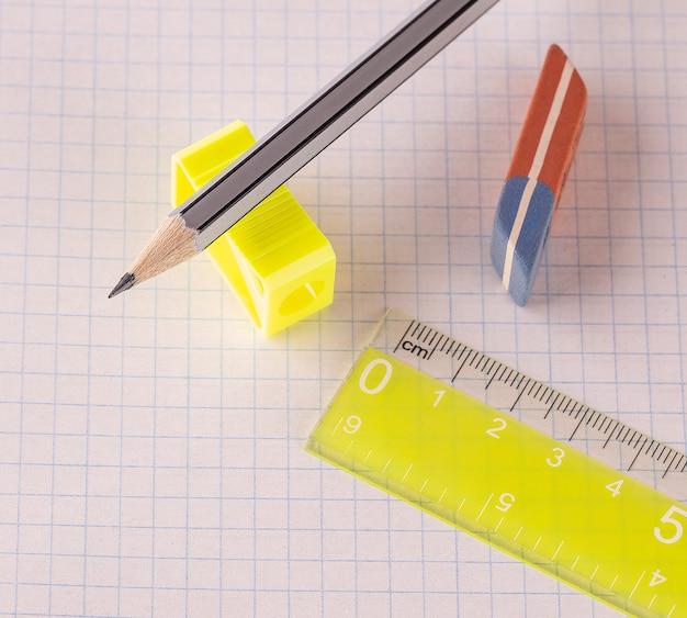 De potloden met puntenslijper en gum met liniaal geïsoleerd op wit