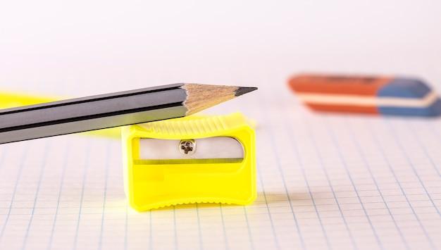 De potloden met puntenslijper en gum op wit wordt geïsoleerd