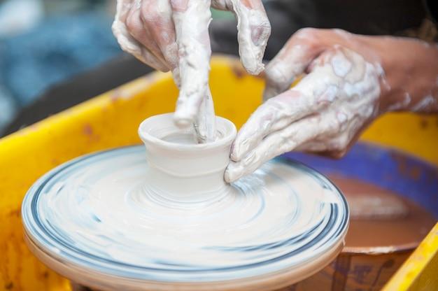 De pottenbakker maakt potten op de pottenbakkersschijf. de beeldhouwer in workshop maakt close-up van het kleiproduct. handen van de pottenbakker.
