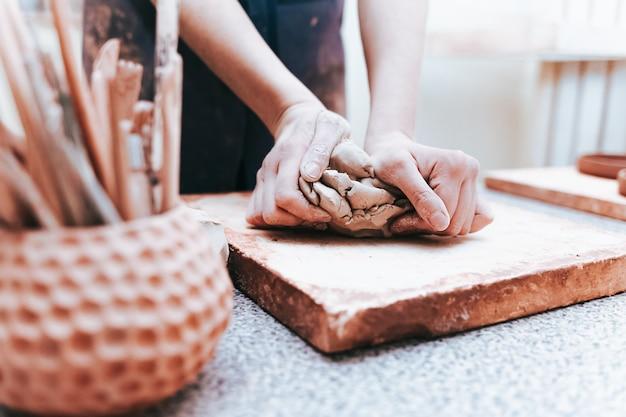 De pottenbakker van de vrouw kneedt klei om keramische producten te creëren.