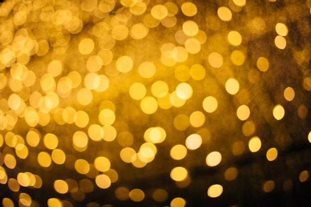 De prachtige achtergrond van het sprankelende licht van het gouden licht 's nachts