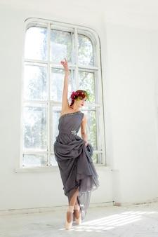 De prachtige ballerina danst in een lange grijze jurk