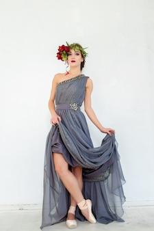 De prachtige ballerina poseren in lange grijze jurk