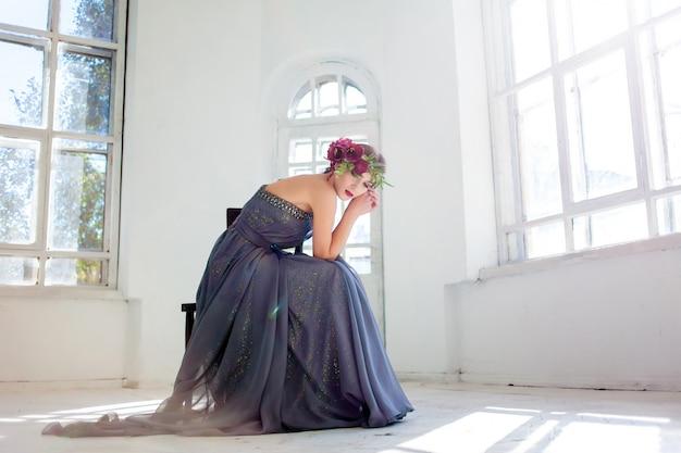 De prachtige ballerina zit in lange grijze jurk