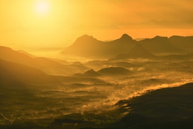De prachtige berg van de landschapszonsopgang met de gele gouden hemel van de mistmist