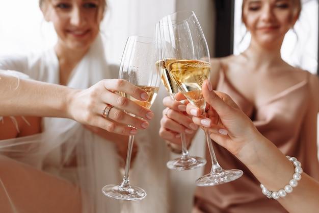 De prachtige bruid met de beste bruidsmeisjes houdt een bril vast en drinkt champagne in de hotelbadkamer bij het raam