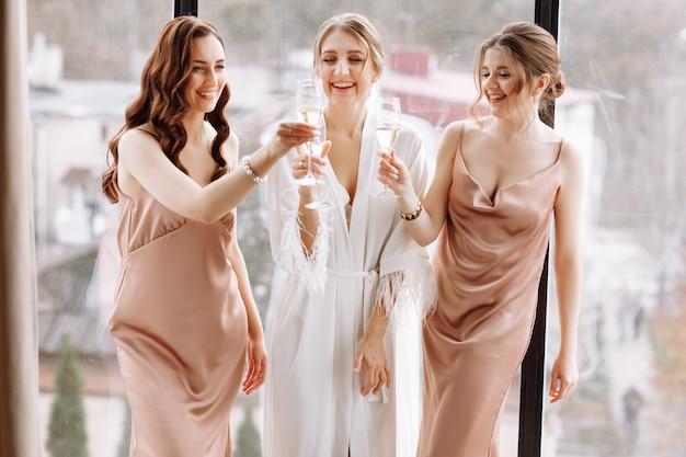 De prachtige bruid met de beste bruidsmeisjes houdt een bril vast en drinkt champagne in de hotelkamer bij het grote raam.