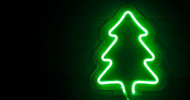 De prachtige kerst achtergrond met neon kerstboom op het houten bureau