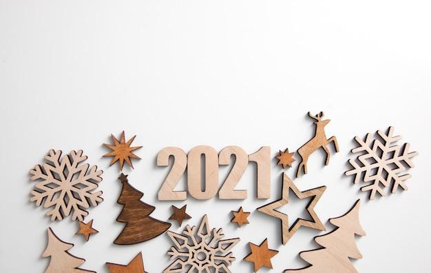 De prachtige kerstachtergrond met veel kleine houten versieringen en houten cijfers 2021 op het witte bureau.
