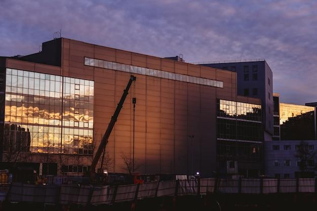 De prachtige kleurrijke zonsonderganghemel wordt weerspiegeld door het met glas overdekte bedrijfsgebouw