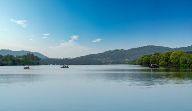 De prachtige natuurlijke omgeving en houten boten van west lake in hangzhou