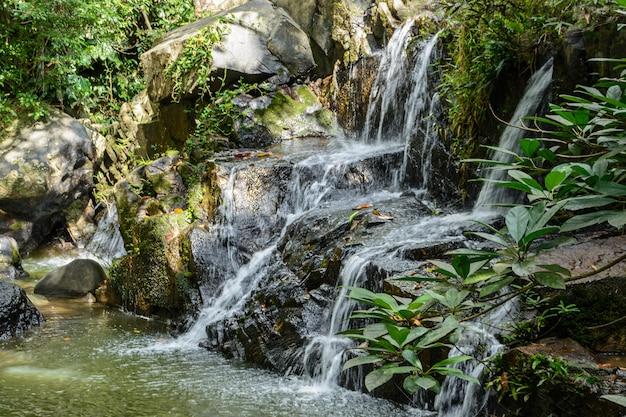 De prachtige watervallen, stroomversnellingen en bergstromen in het tropische bos in yanoda park, sanya city. hainan-eiland, china.