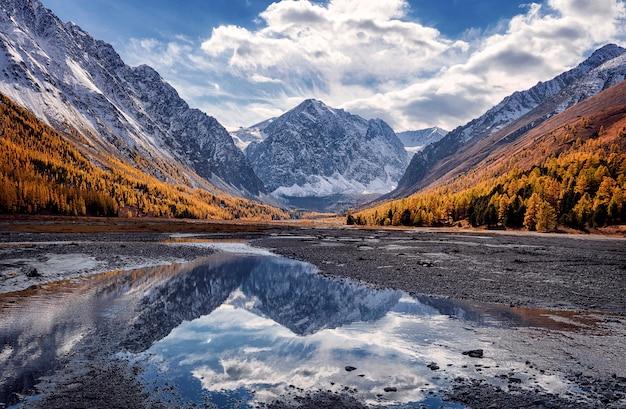 De prachtige weerspiegeling van de piek van karatash en wolken in een klein stroompje. aktru. altai gebergte. siberië. rusland.