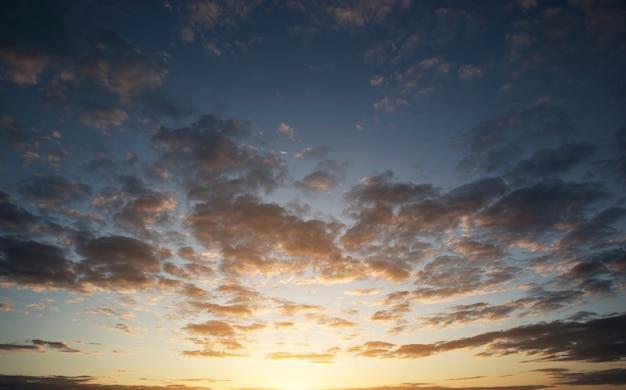 De prachtige zonsondergang aan de hemel en veel grote donkere wolken