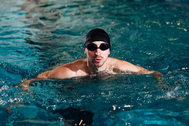 De praktijk van de hoge hoek mannelijke zwemmer bij bassin