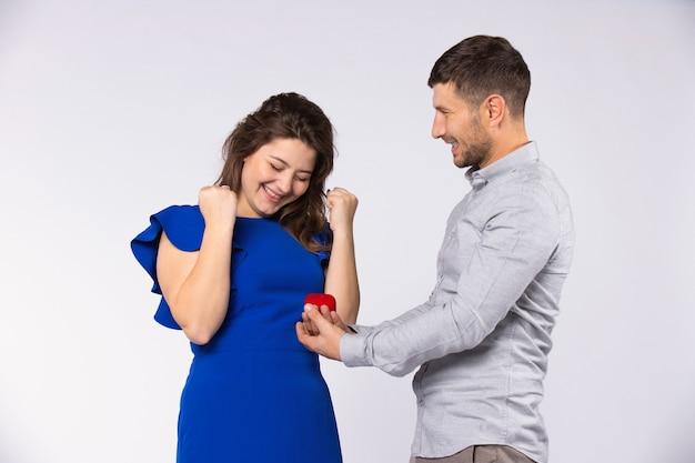De prestatie van het paar. de man stelde een meisje ten huwelijk en presenteerde de verlovingsring op valentijnsdag. grijze achtergrond.