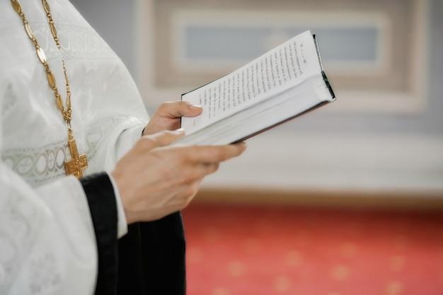 De priester houdt een gebedenboek vast voor de doop in de kerk in rusland
