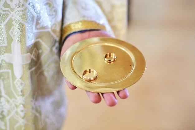 De priester houdt plaat met gouden trouwringen