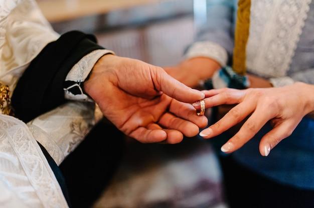 De priester verandert de trouwringen aan de vingers van de bruid en bruidegom.