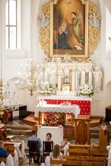 De priester viert huwelijksmassa bij de kerk
