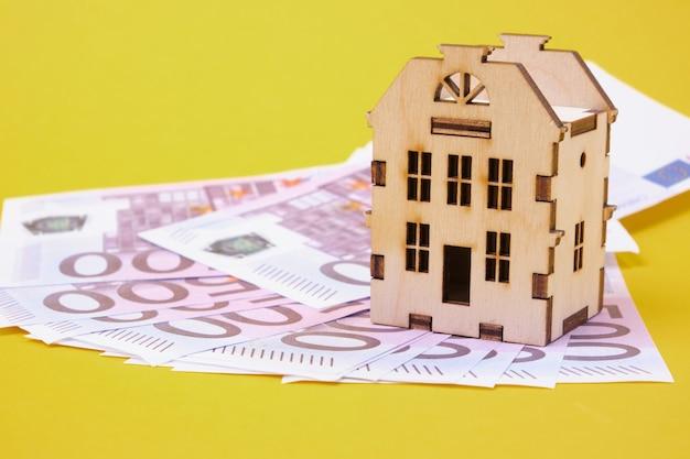 De prijs van het onroerend goed. houten speelgoed huis op een pak van 500 euro rekeningen gele achtergrond
