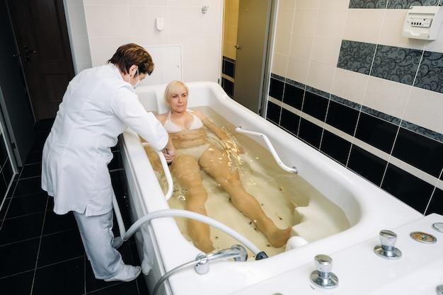 De procedure van onderwaterdouchemassage in de badkamer. meisje over de procedure van onderwatermassage.