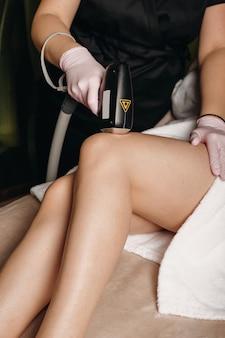De procedure voor het epileren van de benen gebeurt in een moderne salon met apparatuur op de benen van de cliënt waardoor deze haarloos worden