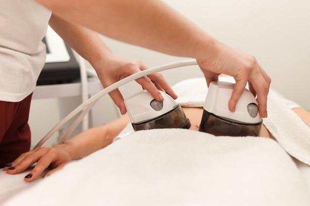 De procedure voor vacuüm anti-cellulitis massage van de buik in een cosmetische kliniek
