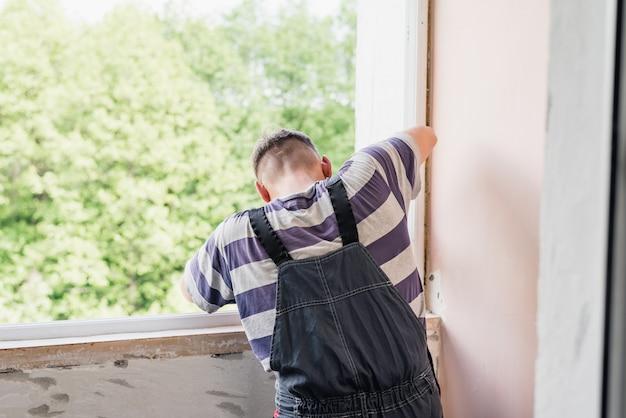 De proces mannelijke arbeider die venster in een huis herstellen, sluit omhoog