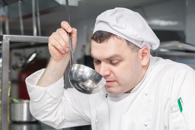 De professionele chef-kok in wit uniform probeert schotel