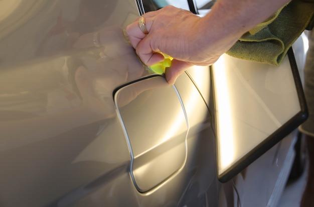De professionele technicus van de deukhersteller zonder verf repareert deuken op de carrosserie. handen van automonteur. proces van het verwijderen van deuk op autospatbord na een ongeval. pdr verhuizingscursus training.
