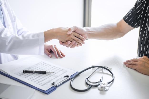 De professionele vrouwelijke arts in witte laag het schudden hand met patiënt na succesvol adviseert behandelingsmethoden na resultaten over het probleemziekte, geneeskunde en gezondheidszorgconcept