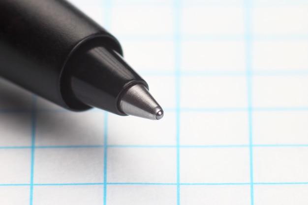 De punt van de pen om op de achtergrond van wit papier in de doos te schrijven
