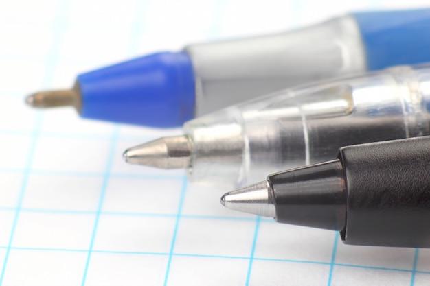 De punt van een pen voor het oppervlak van het witte papier