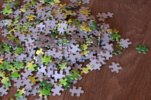 De puzzel ligt verspreid over de houten vloer Premium Foto