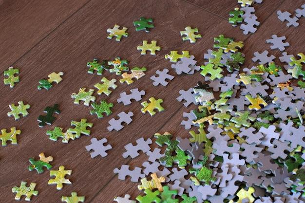 De puzzel met groene onderdelen ligt verspreid over de houten vloer