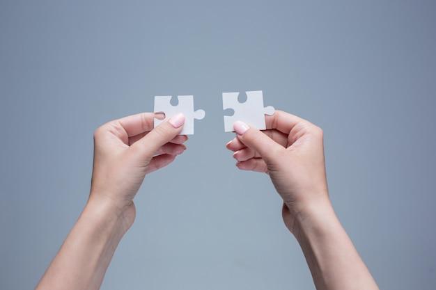 De puzzels in handen op grijs