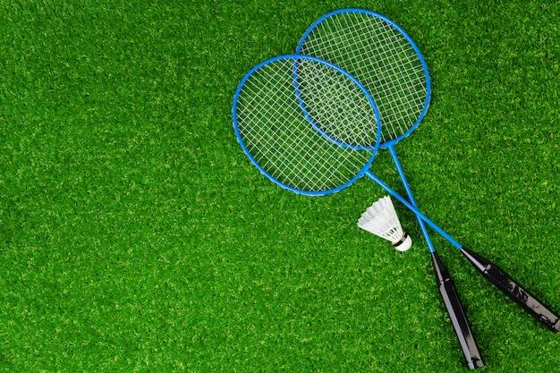 De rackets en de shuttle van het badminton op gras
