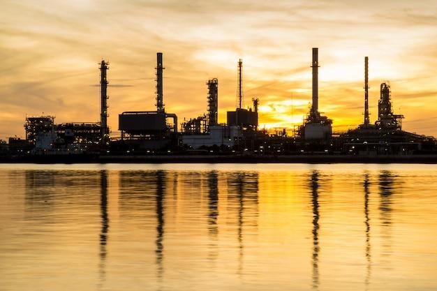 De raffinaderijfabriek van de olie in silhouet en zonsopganghemel