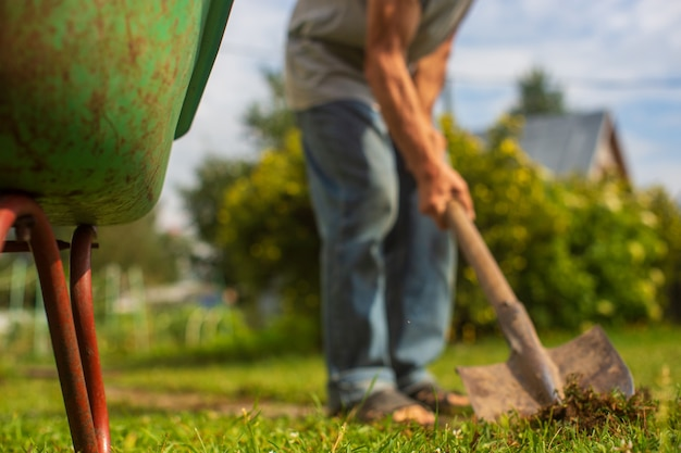 De rand van de kruiwagen in de tuin. op de achtergrond is een boer met een schop de grond aan het graven. landbouw en tuinieren concept.