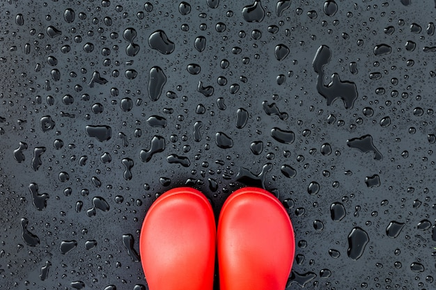 De randen van de rode rubberen laarzen liggen op een natte, natte ondergrond bedekt met regendruppels