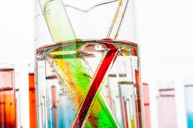 De reageerbuizen met kleurrijke chemische producten sluiten omhoog in laboratorium