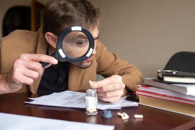 De rechercheur is op zoek naar afdrukken op de plaats delict