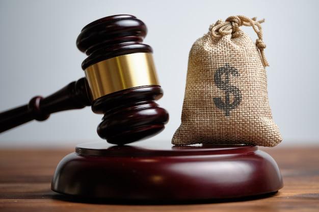 De rechter hamert naast een zak met geld.