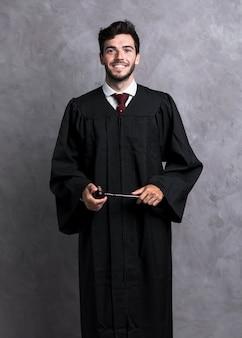De rechter van vooraanzichtsmiley die in robe houten hamer houdt