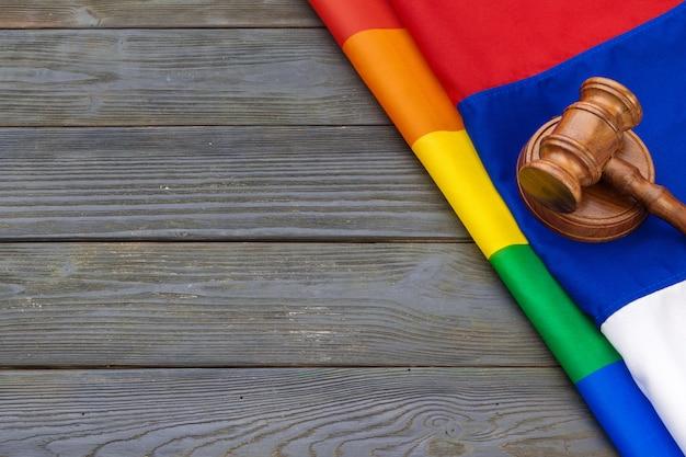De rechterhamer, de wet en de rechtvaardigheid van woden met lgbtvlag in regenboogkleuren en houten achtergrond